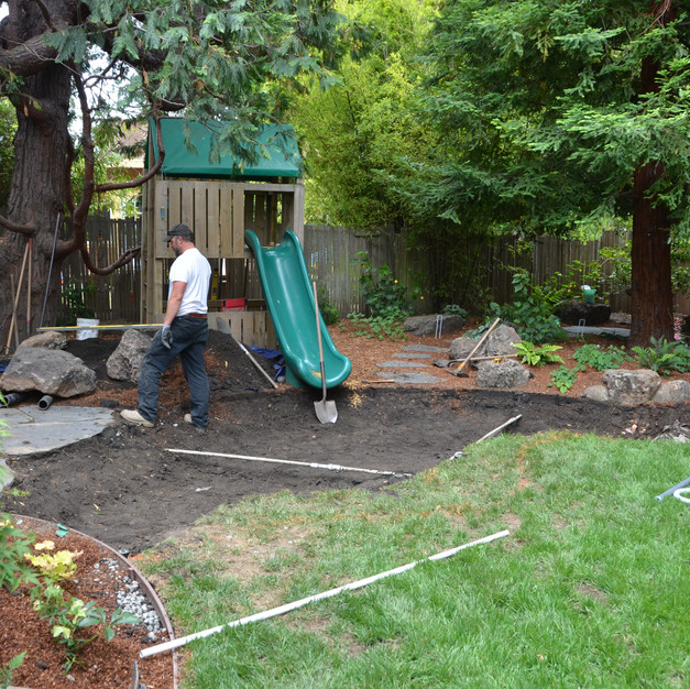 a swampy part of existing lawn is removed for rain garden installation