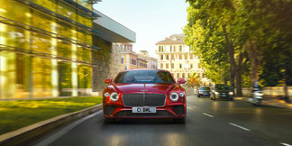 4-continental-gt-driving-past-city-park-