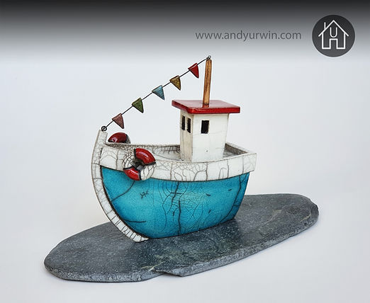 Handmade ceramic Raku turquoise trawler with a wooden mast, ceramic flags and detachable lifesavers on a Welsh mine slate base