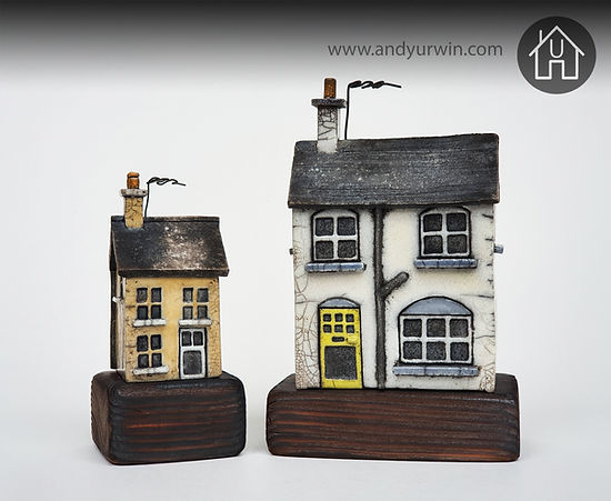 Detailed handmade ceramic Raku houses on polished wood base