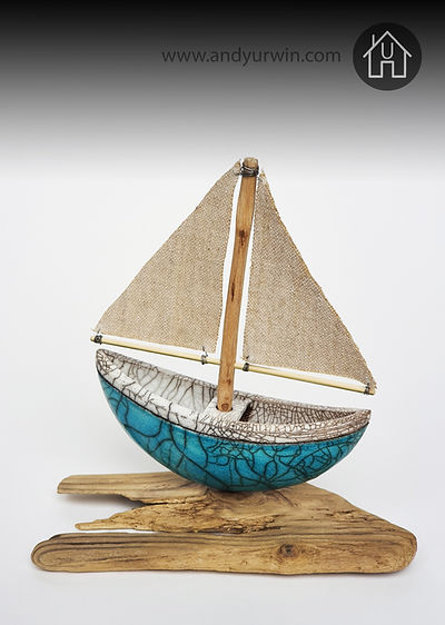 Handmade ceramic Raku turquoise sail boat with fabric sails and driftwood mast and base.
