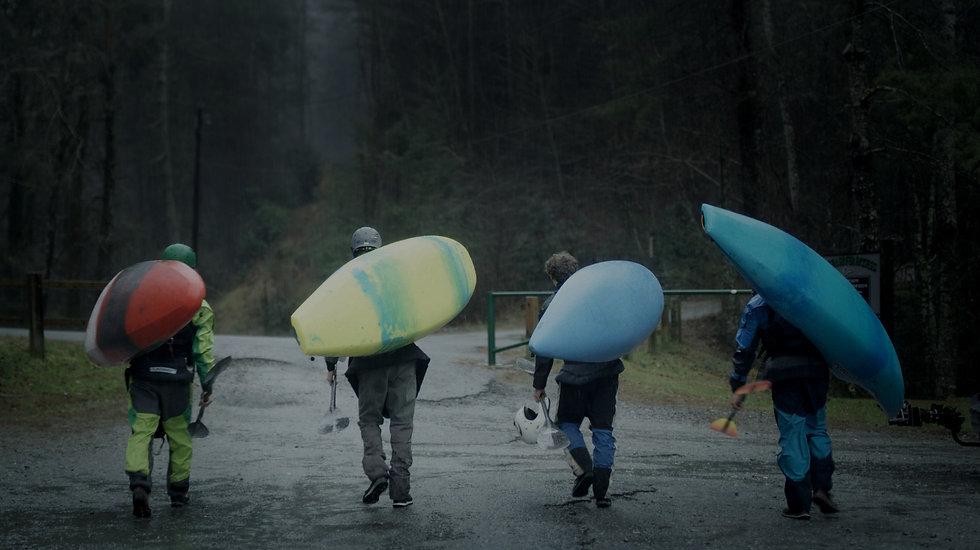 group of kayakers carrying kayaks