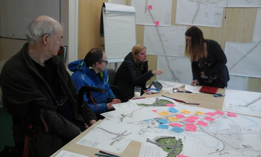 3 members of SAAP look at plans and drawings with Kayleigh Webster, project lead of Walk, Cycle, Live project