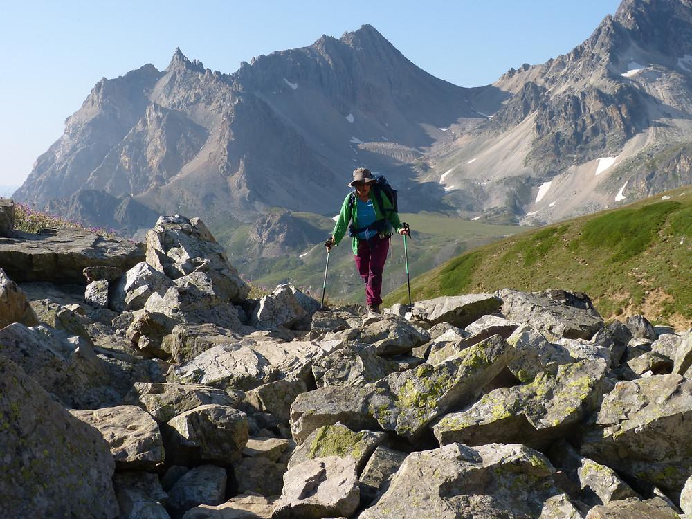 Randonneur marchant de façon déterminée avec en fond les montagnes du massif