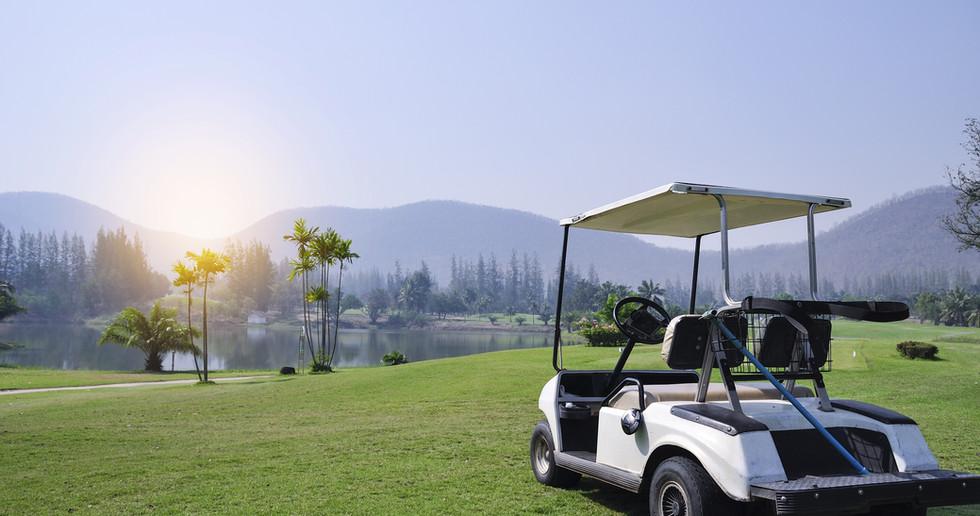 golf car on green grass Mountain backdro