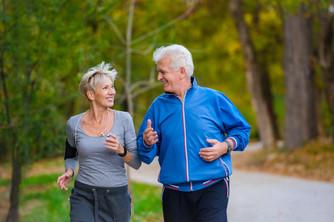 Smiling senior couple jogging in the par