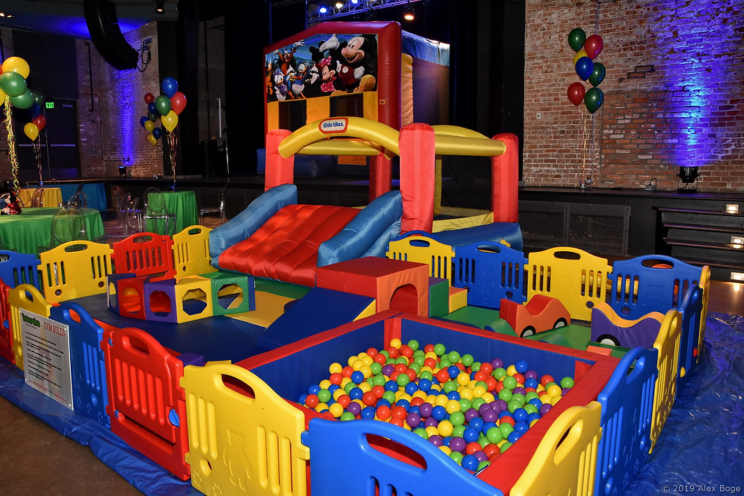 Totcercise mobile soft gym play area set up with plastic barrier, inflatable bounce house and soft cubes to play with