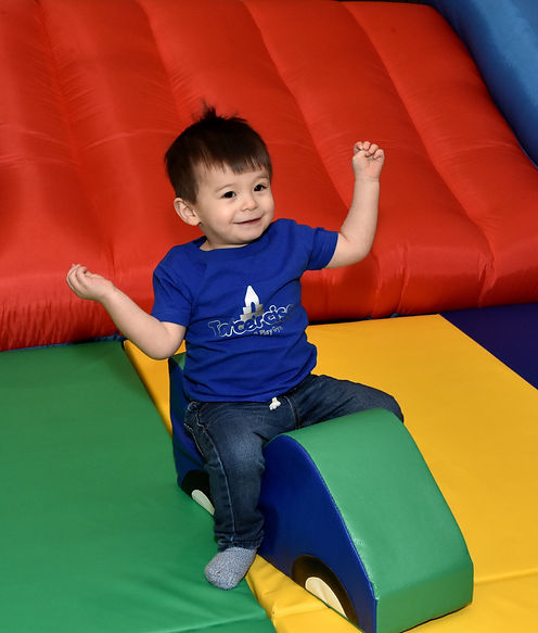 A young boy in a blue shirt with the totcercise logo enjoying riding on a soft cube that comes with all totcercise packages