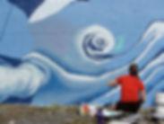 artist painting a whale mural in Seward, Alaska, public art.