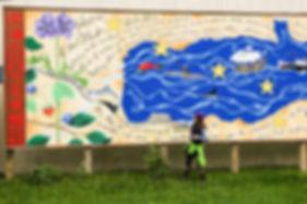 Artist and tour guide Justine Pechuzal explains the Alaska Statehood Mural at the Seward post office.
