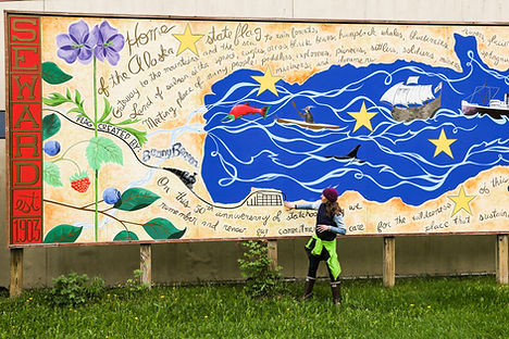 Artist and tour guide Justine Pechuzal explains the Alaska Statehood Mural at the Seward post office.