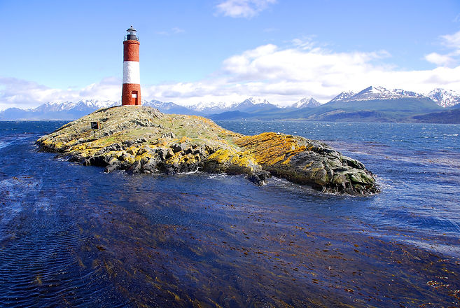 Red and white lighthouse in blue sky in the Beagle Channel Ushuaia Patagonia Argentina.jpg