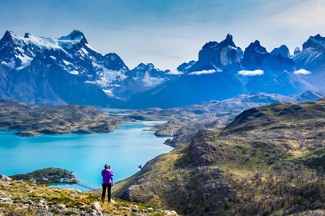 Woman at mirador Condor enjoying hiking and top view of mountains Los Cuernos  and turquoise lake Pe