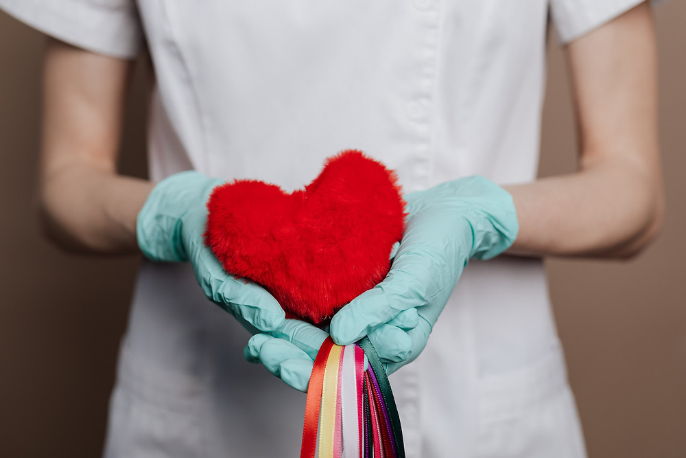Hands holding red heart with strings