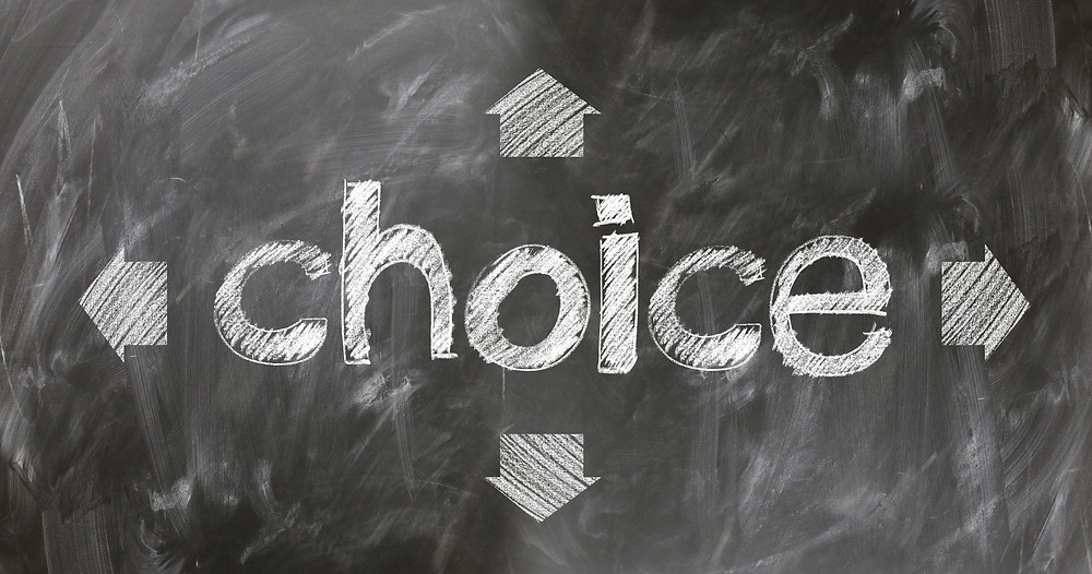 "The word ""choice"" written on a blackboard with four arrows reflecting possible decisions"