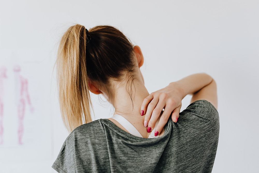 Woman holding hand on neck to alleviate pain