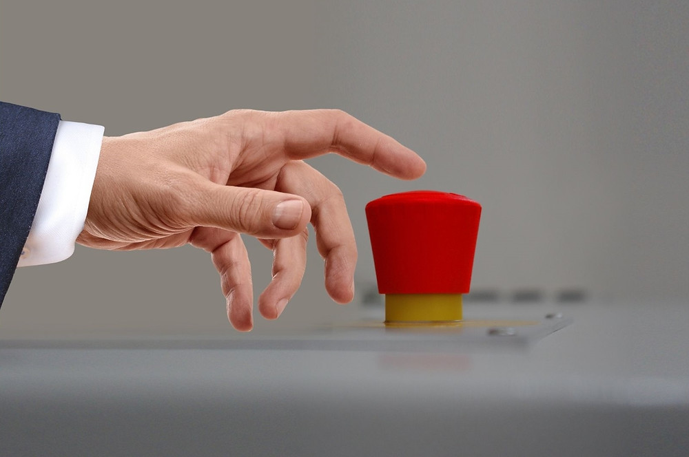 Hand pressing red trigger button