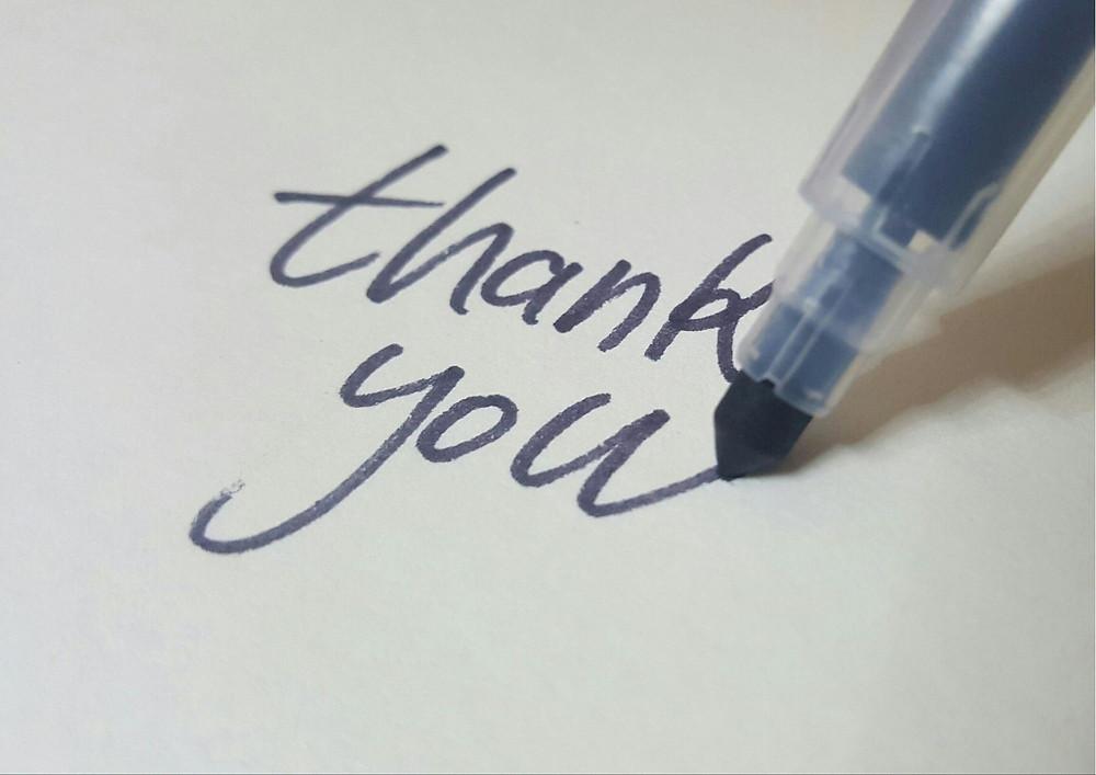 Pen writing thank you on white background