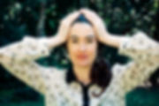 Holistic Therapist Lauren Joy Wilson with her hands on her head practising mindfulness in nature