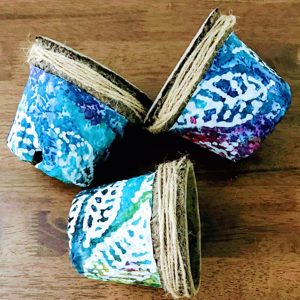 Photo of four inch plant pots covered in decorative fabric with colorful leaf pattern. Click link to visit shop and purchase pots or other eco-friendly gardening supplies.