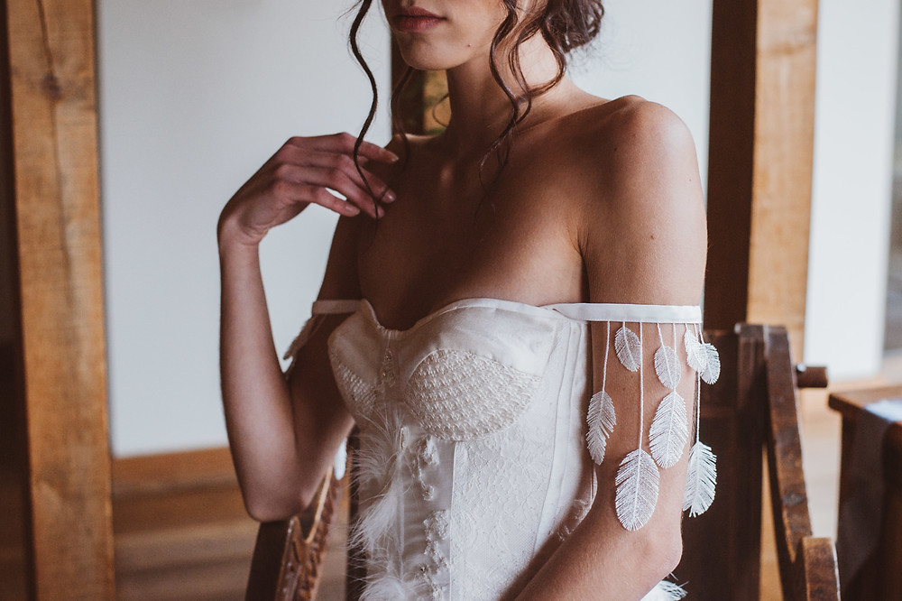 A bridal corset with feather details.  Jessica Turner Designs