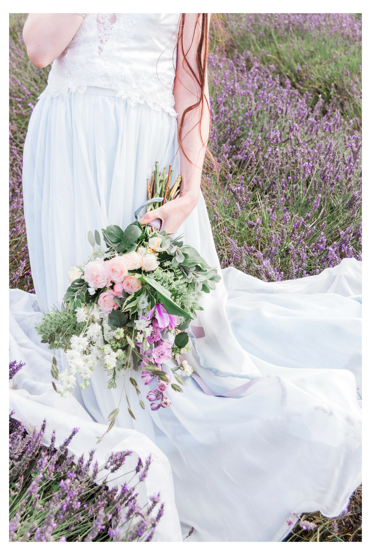 A bridal bouquet with purple flowers.  'Hollyhock' by Jessica Turner Designs, a lace boho bridal separate worn with a floaty chiffon subtle blue skirt.
