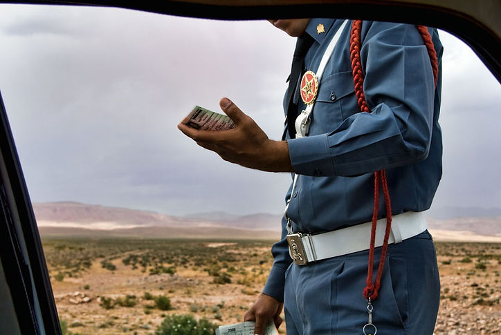 Moroccan Policeman on the Road A Policeman checks the ID documents. Police checkpoints are very common on the roads of the desert and the atlas. ©David Arnoldi