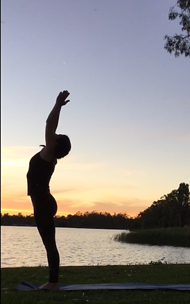 Woman practising yoge by a lake at sunset