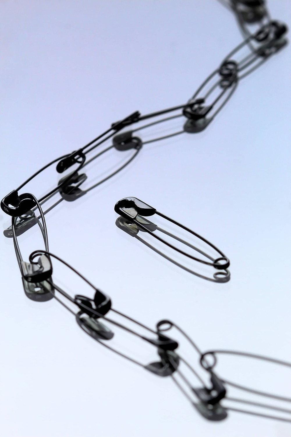Chain of safety pins, one separated