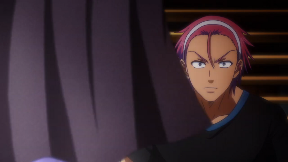 A man with magenta hair named Kengo, looking at a piece of cloth