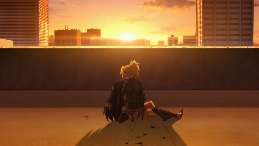 Two girls on a rooftop with a sunset in front of them