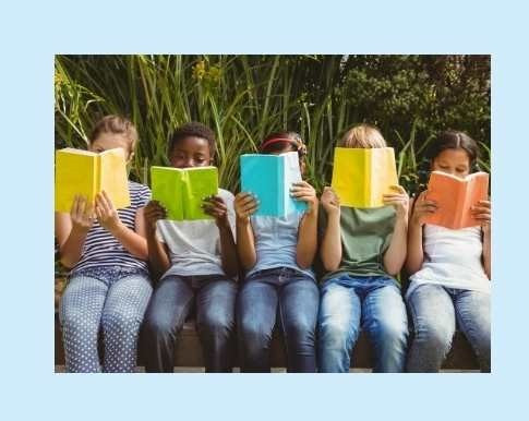 Children sat in a park all reading