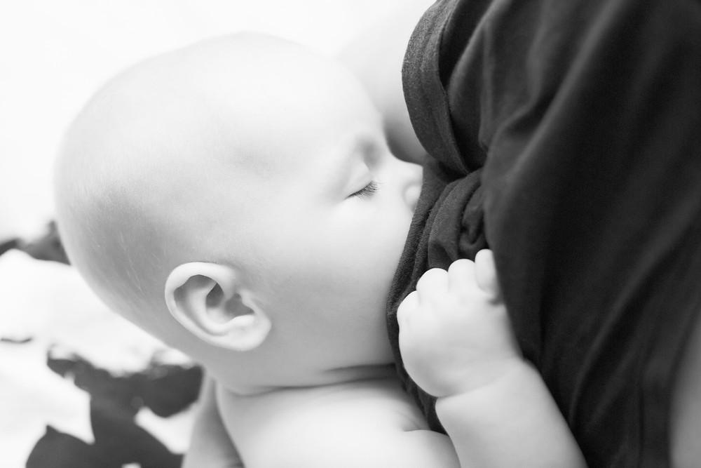Postpartum Doula demonstrating correct breastfeeding latch