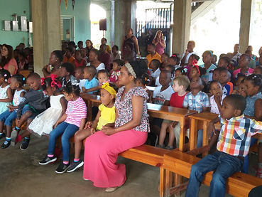 A teacher sits with her students at weekly Chapel