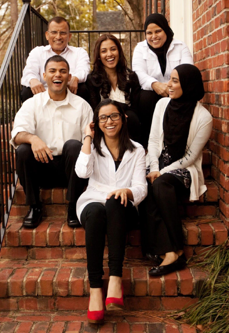 Family of 6 smiling on a stoop.