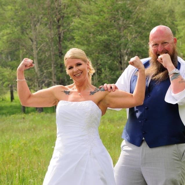 Couple on their wedding day. She is doing the muscle pose!