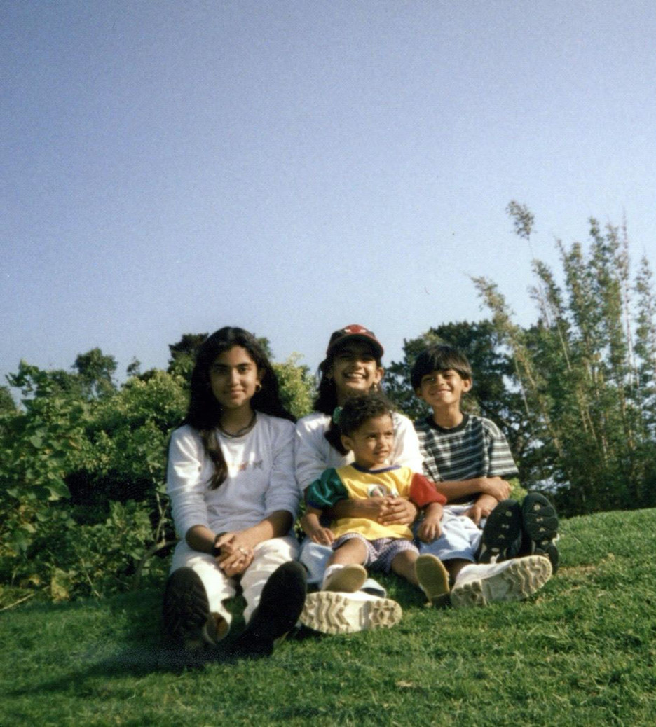 Four siblings smiling and sitting in the grass.