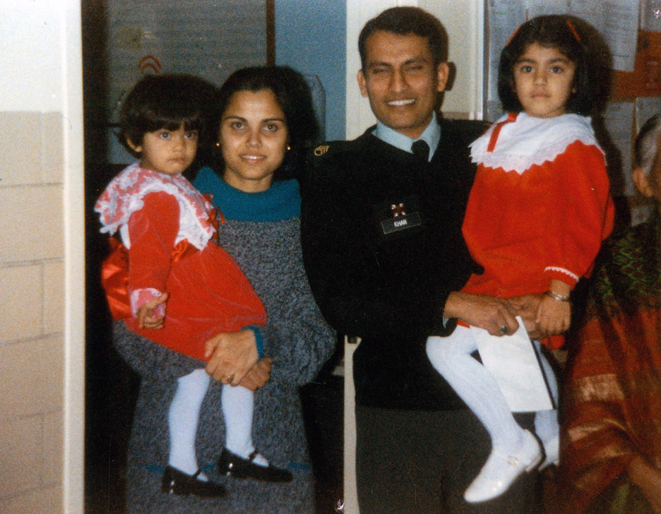 Two little girls in matching red dresses and their parents