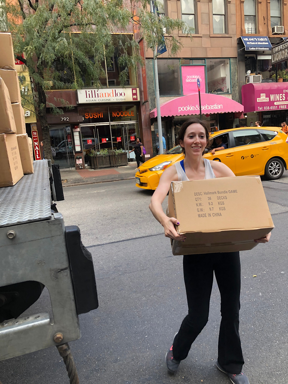 Cassie carrying a box of board games