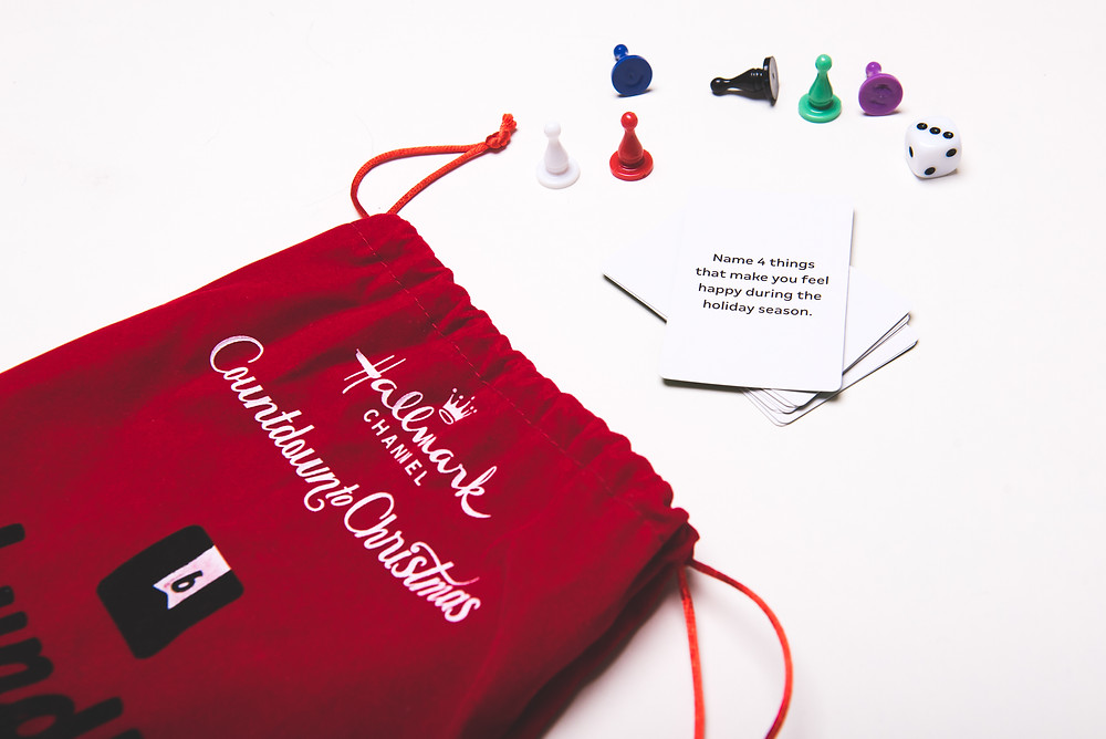Drawstring bag with playing cards, game pieces, and die.