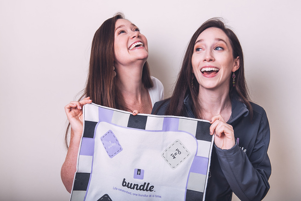 Founders Jackie and Cassie laughing and holding a personalized Bundle board game.