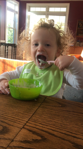 Messy toddler feeding himself with a spoon