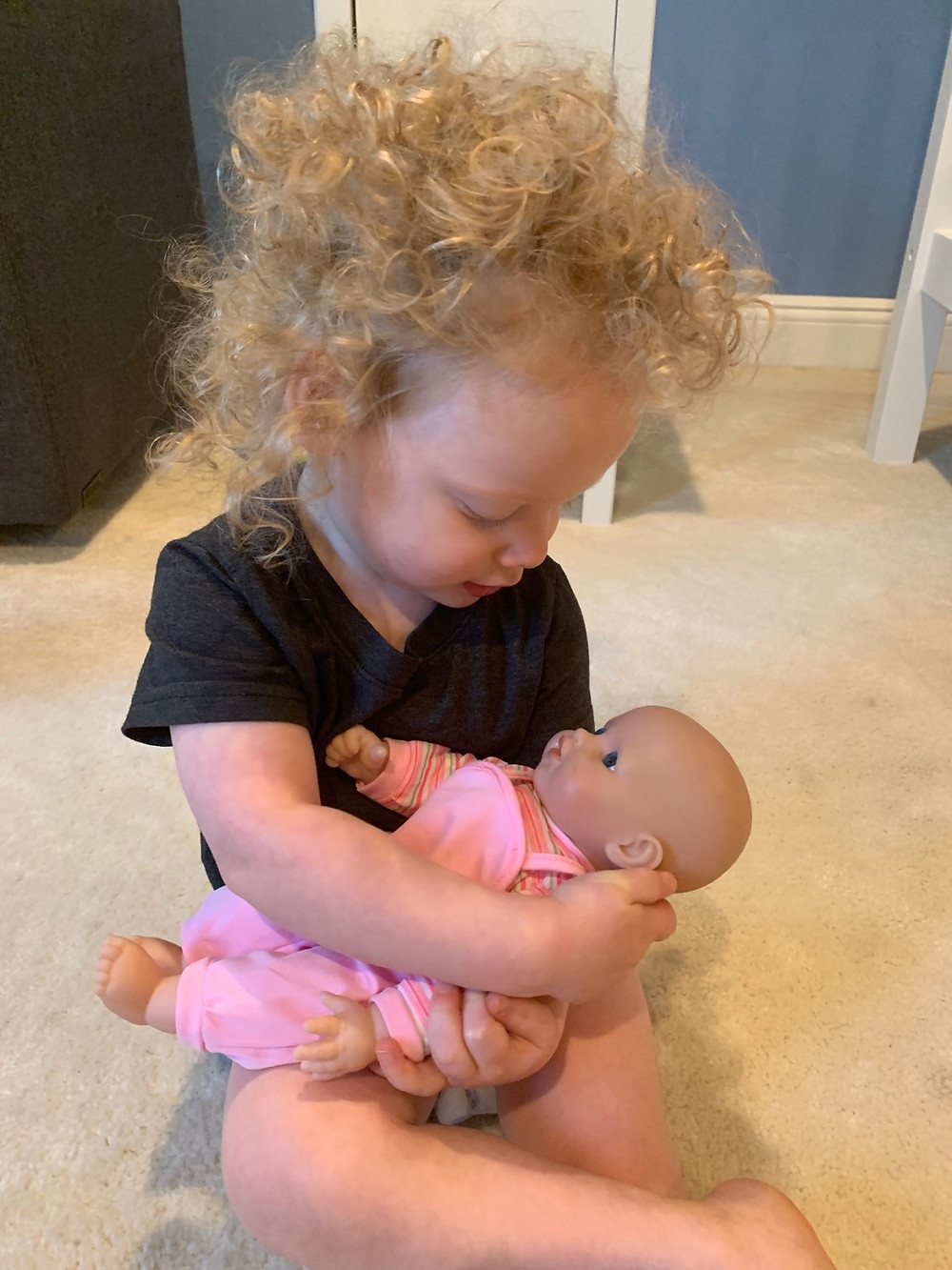 Toddler boy holding a baby girl doll