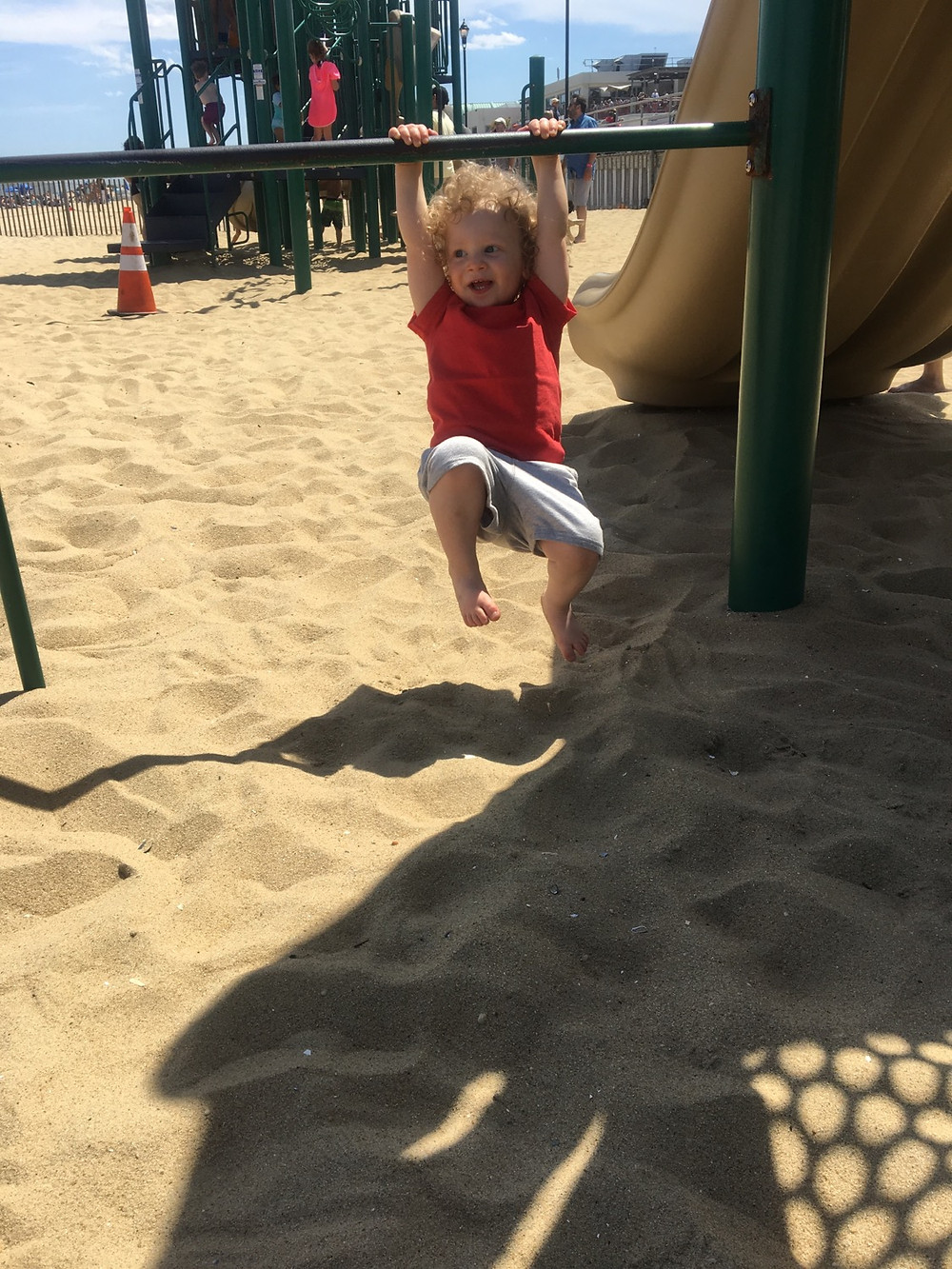Little boy swinging from the bars on a playground on the beach