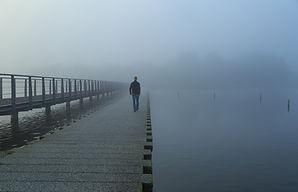 Ein Mensch, der über einen Steg über das Wasser geht