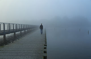 man walking down a boardwalk over the water