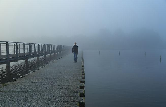 Uomo cammina su pontile avvolto dalla nebbia