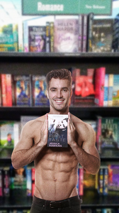 "Andrew Biernat holding romance novel, ""The First Taste"", in front of Barnes and Noble book shelf."
