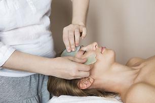 Young woman have face guasha treatment a