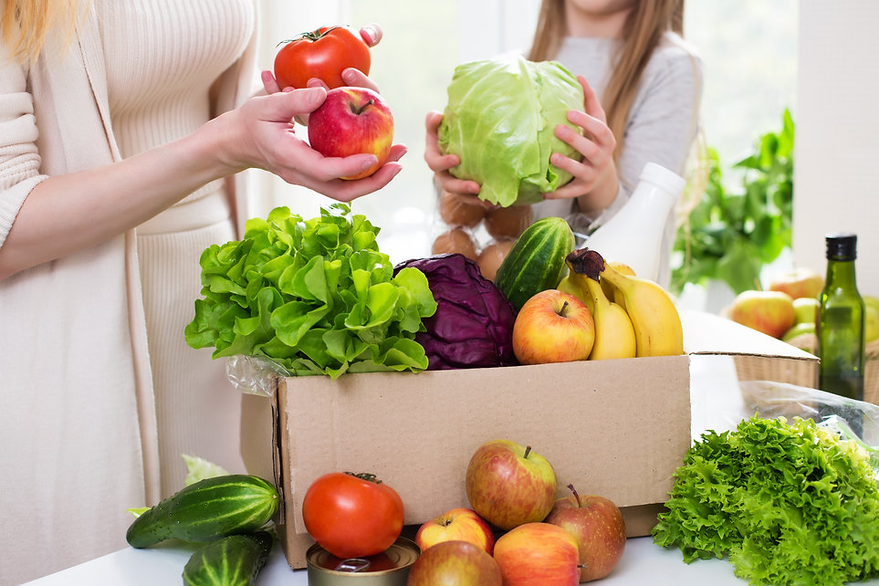 Food delivery. Mom and daughter unpack a box of vegetables and fruits. Online order from